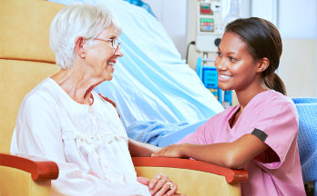 elder woman and caregiver smiling to each other