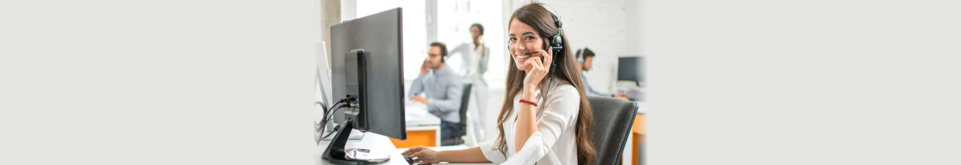 Young friendly operator woman with headsets working